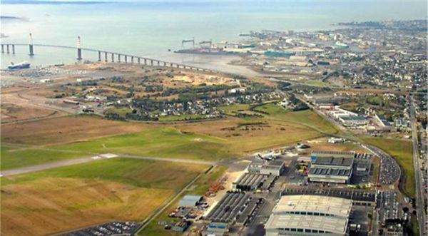 Sur cette photo datant de quelques années, on peut observer de gauche à droite et de bas en haut, la piste de l'aéroport, les usines Airbus, le nouveau port de Saint-Nazaire, le Pont de Saint-Nazaire, les chantiers navals STX, et la ville de Saint-Nazaire (5)