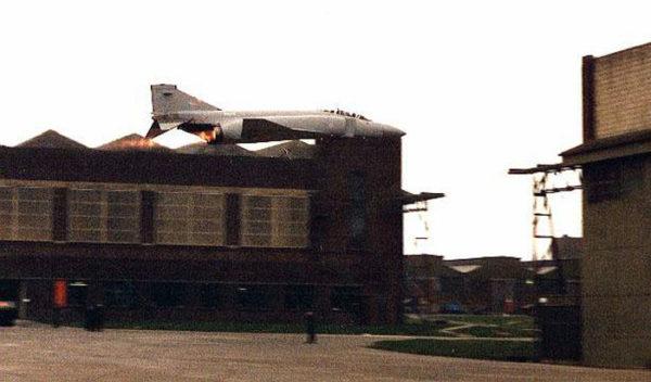 Un Phantom II de la RAF en passage bas, post combustion allumée, entre 2 hangars de la base de St Athan (Galles)