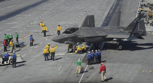 Largement couvé par les personnels du pont d'envol, ce F-35C a les ailes en partie repliées.