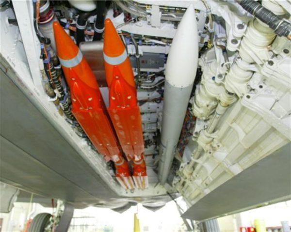 Un AIM-120, en gris, accompagné par quatre GBU-39 orange, dans la soute d'un F-22 raptor