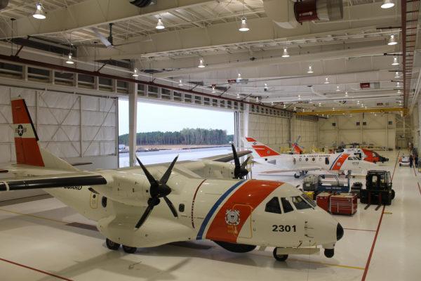 Airbus Military HC-144A, Dassault HU-25C, et Sikorsky MH-60J dans un hangar commun de CGAS Cape Code.