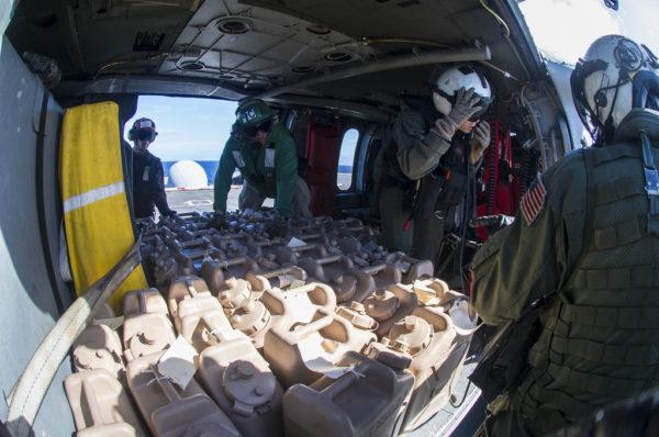 Des jerricans remplis d'eau potable sont chargés à bord d'un MH-60S Seahawk.