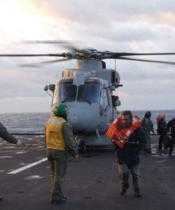 Des passagers sauvés sont débarqués d'un hélicoptère militaires italiens.