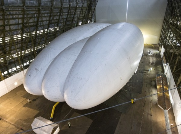 CARRINGTON, ENGLAND - FEBRUARY 28:  Mike Durham, the Technical Director at Hybrid Air Vehicles, admires the helium-filled 'Airlander' aircraft in a giant airship shed on February 28, 2014 in Cardington, England. The Airlander, which was originally developed for the US military before the project was cancelled due to budget cuts, is the world's longest aircraft at 92 meters. Although slow moving compared to conventional aircraft, the Airlander is able to carry large payloads over long distances very efficiently. Hybrid Air Vehicles' project to develop the technology further is being funded by a Government grant as well as private finance from individuals including Bruce Dickinson, the lead singer of the band Iron Maiden.  (Photo by Oli Scarff/Getty Images)