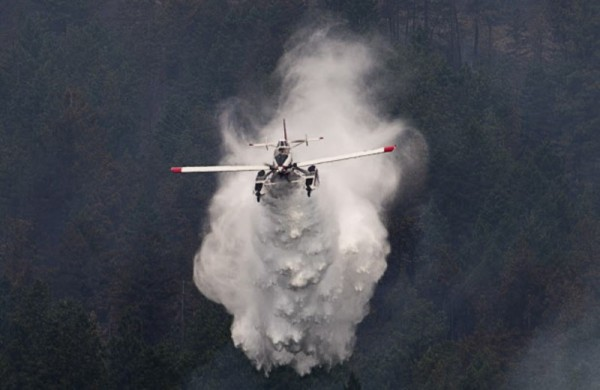 A water bomber drops water on a hillside in West Kelowna, B.C. Friday, July, 18, 2014. Over 2500 residents of the area were evacuated when the fire suddenly grew in size threatening nearby homes. THE CANADIAN PRESS/Jonathan Hayward ORG XMIT: JOHV113