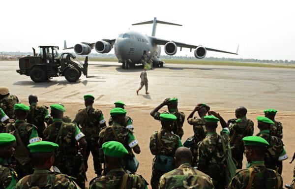 Des soldats rwandais patientent avant d'embarquer dans un Boeing C-17A américain.