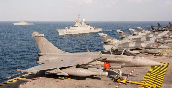 Les avions de combat français parqués sur le pont d'envol du CDG. En arrière-plan on aperçoit les deux frégates saoudiennes.