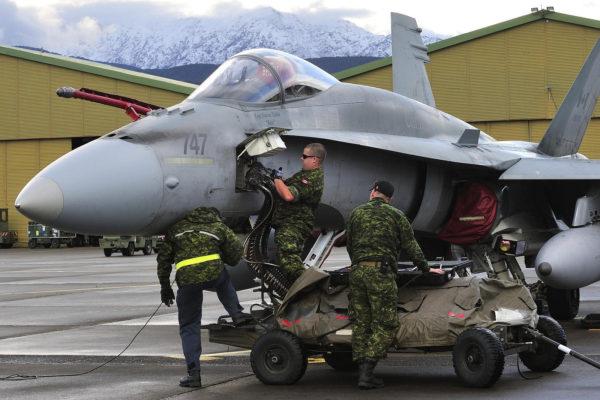 Des armuriers canadiens approvisionnent le canon d'un CF-188 Hornet, en arrière-plan on distingue le relief corse.
