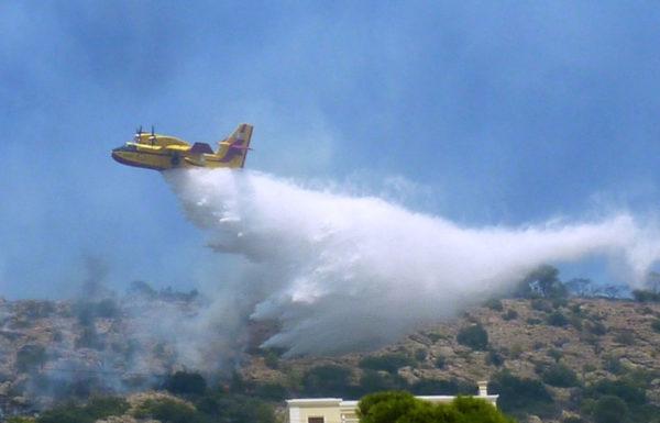 Bombardier CL-415 grec larguant sa charge d'eau sur une cible péri-urbaine.
