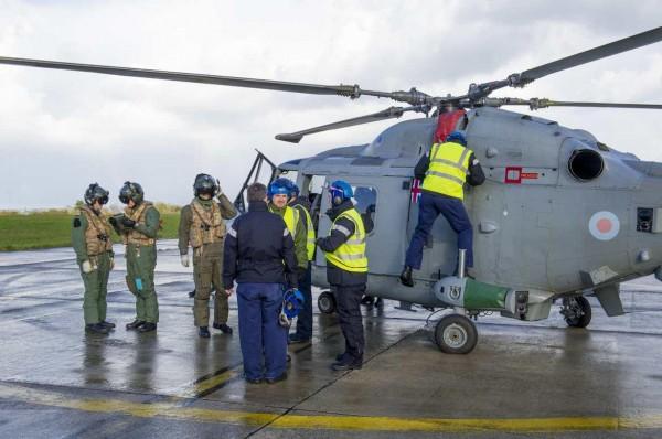 Personnels britanniques et français s'affairent autours d'un Lynx de la Royal Navy.