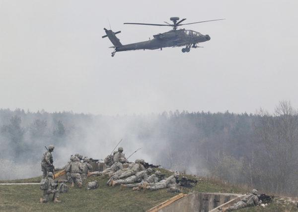 """Image typique de l'US Army in Europe : un Apache """"en appui"""" d'un exercice terrestre."""