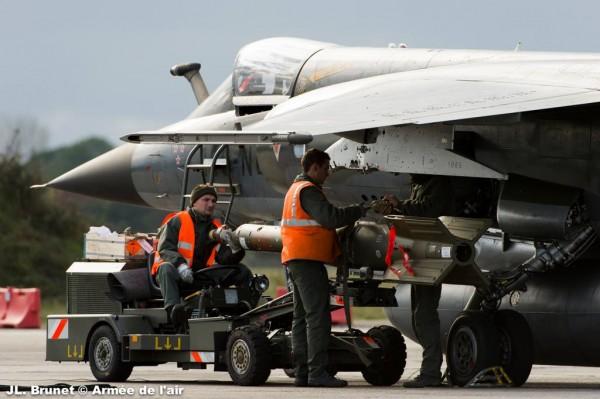 Deux armuriers gréent un Mirage F1-CR au moyen d'une arme à guidage laser GBU-16 d'origine américaine.