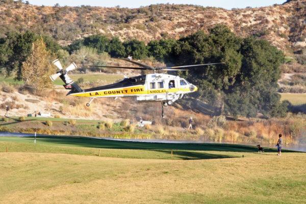 Un Sikorsky S-70 des pompiers du comté de Los Angeles avitaille en eau au-dessus d'un terrain de golf.
