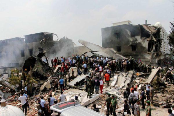 Les équipes de secours s'activent autour de la carcasse encore fumante de l'avion-cargo.