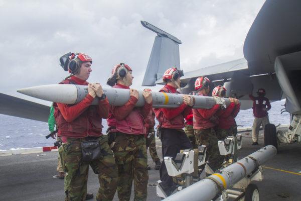 Des armuriers de l'US Navy installent un AMRAAM sur un Boeing F/A-18E Super Hornet en mer.