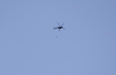 Sur ce (mauvais) cliché on distingue un baril ou une bombe chutant d'un hélicoptère Hip au-dessus d'Alep.